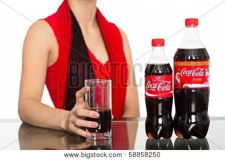 NAKHODKA, RUSSIA - JANUARY 18, 2014: Girl holding a glass of Coca-Cola on the table is a bottles of Coca-Cola. Coca-Cola is a very popular carbonated soft drink sold in stores, restaurants worldwide