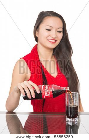 NAKHODKA, RUSSIA - JANUARY 18, 2014: Cheerful Asian girl pours a Coca-Cola from a bottle into a glass. Coca-Cola is a carbonated soft drink sold in stores, restaurants, and vending machines worldwide