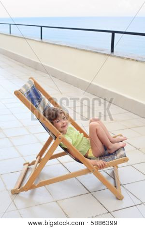 Little Girl In Lounge On Veranda