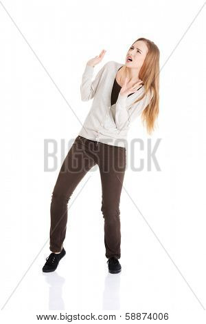 Beautiful casual woman is crouching from sth heavy above her. Isolated on white.