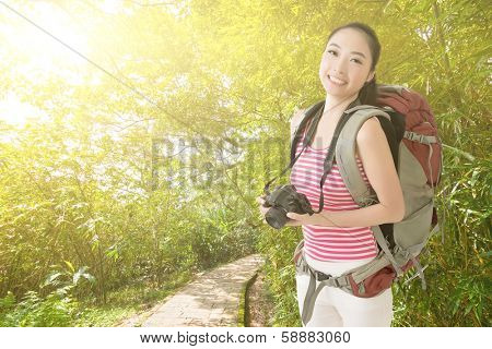 Smiling traveling Asian girl holding a camera and looking at you in the outdoor path.