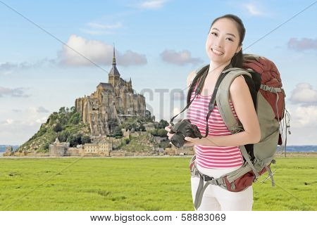 Smiling traveling Asian girl holding a camera and looking at you in front of the famous Mont Saint-Michel, France.