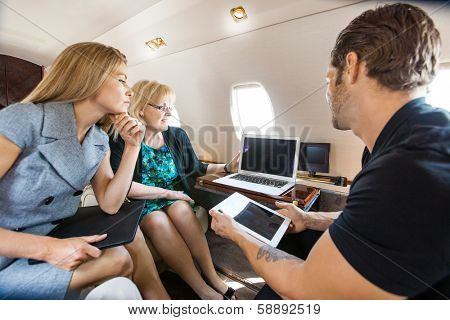 Business people working together on laptop and digital tablet in private jet