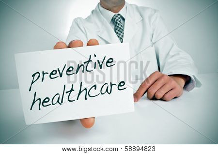 a man wearing a white coat showing a signboard with the text preventive healthcare written in it