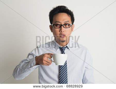 Tired Asian businessman with dark eyes circle holding coffee cup on plain background