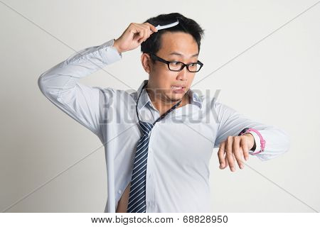 Asian businessman combing hair in morning in hurry, checking time on watch, on plain background.