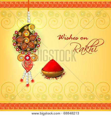 Beautiful pearls decorated rakhi on floral decorated yellow background for Raksha Bandhan celebrations.