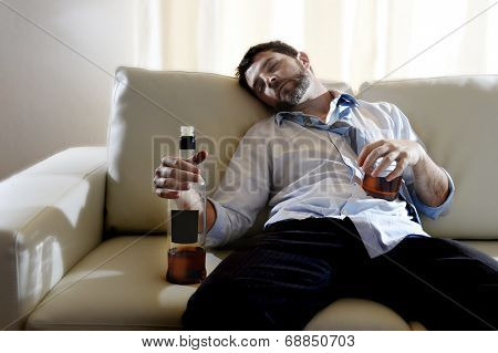 drunk business man at home lying asleep on couch sleeping wasted holding whiskey bottle in alcoholism problem alcohol abuse and addiction concept looking grunge and sick in edgy radical studio lightning poster