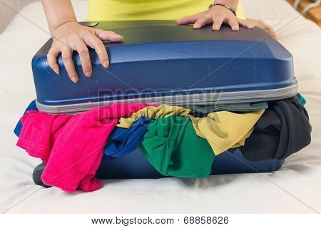 Young woman try to close the overfilled suitcase in the room.
