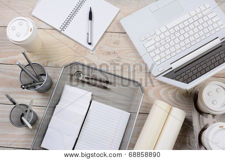 High angle shot of a home office desk with various items including: laptop computer, coffee cups, pad, notebook, pens, pencil cup, envelopes, in tray, compass, The primary color is shades of white.