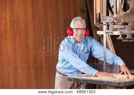 Portrait of senior male carpenter cutting wood with bandsaw in workshop