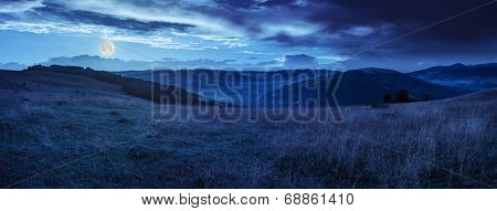 Valley In Mountains  On Hillside Under Sky With Clouds At Night