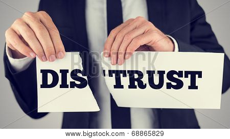 Businessman tearing up a sign saying - Distrust - conceptual image importance of trust and cooperation in successful business. poster