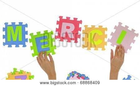 """Hands forming word """"Merci"""" with jigsaw puzzle pieces isolated"""