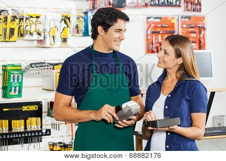 Happy woman with tool set looking at worker swiping credit card in hardware store