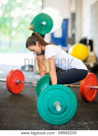 Side view of young fit woman picking barbell at healthclub