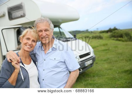 Happy senior couple standing in front of camping car