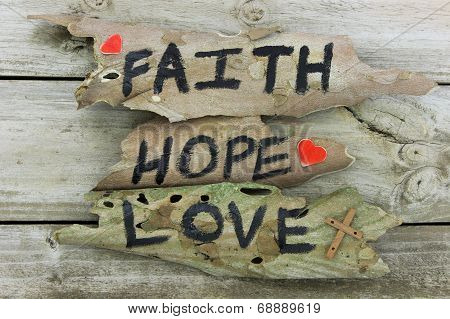 FAITH, HOPE, LOVE sign on rustic wooden background