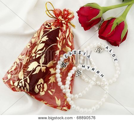 Small bottle of Anointing Oil in Gift Bag, Three Pearl Bracelets and Two Red Roses on White Backgrou