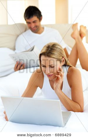 Charming Woman Using A Laptop Lying On Bed