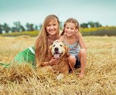 lovely family: mother and daughter with a dog in field poster
