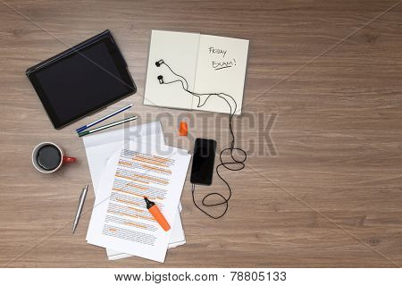 Background, filled with studying materials and copy space on a wooden surface. Items include an electronic tablet,  cup of coffee, pens, markers, a high lighted standard (lorum ipsum) text