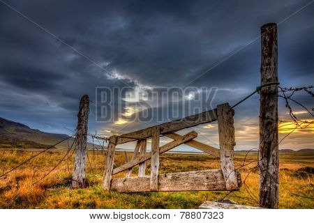 Dilapidated gate on a farm in Iceland with dramatic evening sky in the background