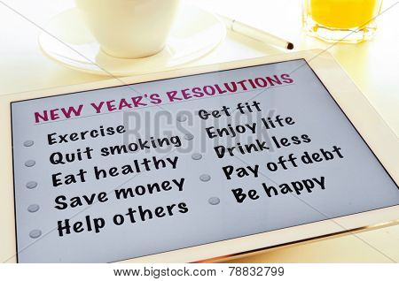 a list of new years resolutions in a tablet, on a table with a cup of coffee and a glass with orange juice