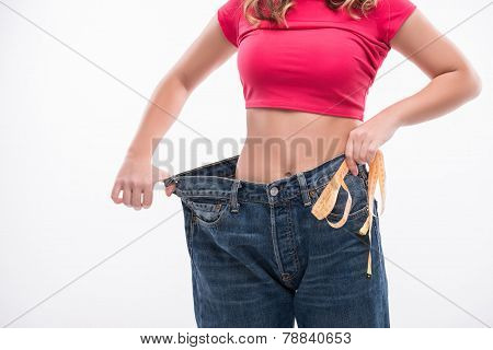 Close-up of slim waist of young woman in big jeans with measuring tape showing successful weight loss isolated on white background, diet concept poster