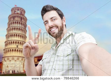 Happy young man taking a selfie photo in Piza, Italy