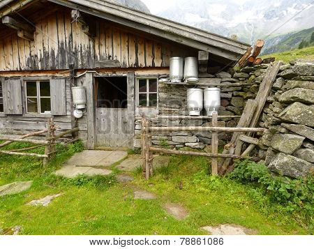 old farmhouse with milk churns in front