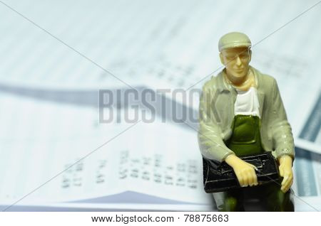 Miniature Figure Sitting On Payroll