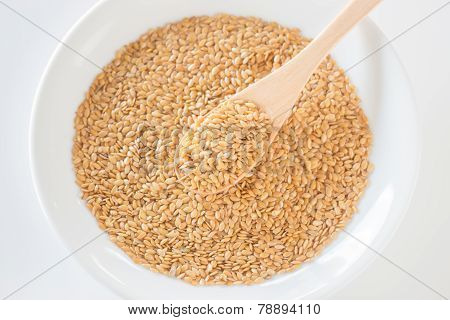 Gold Flax Seeds On A Wooden Spoon
