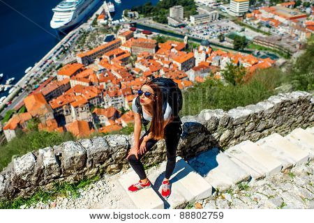 Young woman traveler with backpack climbing up Lovcen mountain near the old city Kotor, Montenegro poster