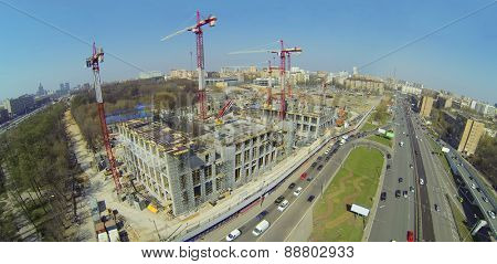 Construction site with lots of cranes next to the road, aerial view