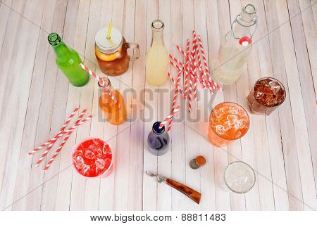 High angle shot of a group of assorted summer drinks. Lemonade, ice tea, soda, cola, orange soda and strawberry soda on a rustic wood table.