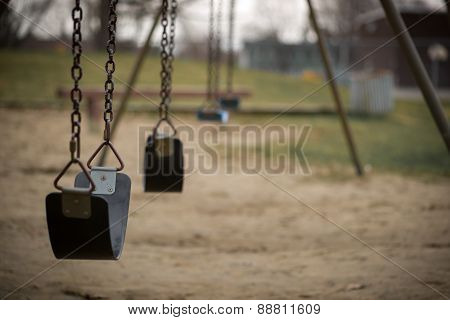 Children's swings hang empty an idle at a playground on a dull overcast day. poster