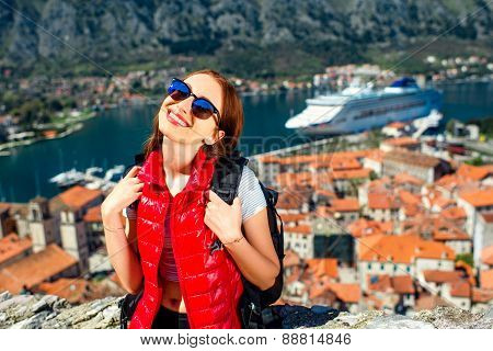 Young woman traveler in red vest with backpack on the Lovcen mountain in old city Kotor, Montenegro poster