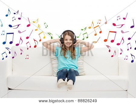 leisure, technology, music and childhood concept - smiling little girl in headphones listening to music sitting on sofa over musical notes