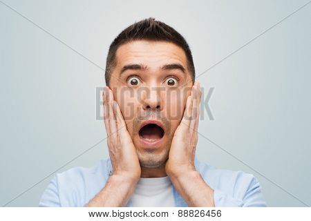 fear, emotions, horror and people concept - scared man shouting and touching his face over gray background