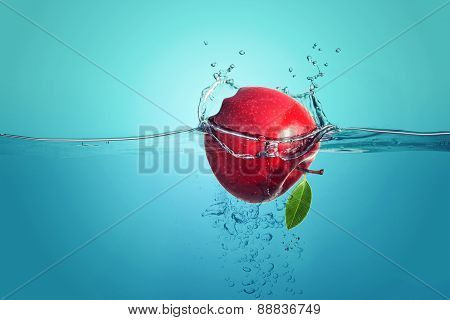 red apple falling into water splach