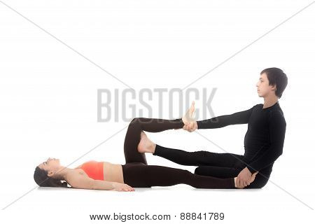 Two sporty people practicing yoga with partner young man coaching helping girl to do stretching exercises for legs poster