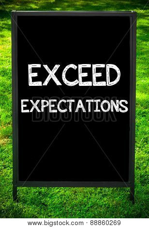 EXCEED EXPECTATIONS message on sidewalk blackboard sign against green grass background. Copy Space available. Concept image poster