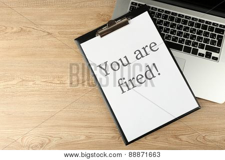 Message You're Fired on laptop keyboard on wooden table, top view