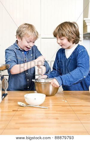 Kids having fun during a baking workshop, whisking dough in a stainless steel bowl during a birthday party