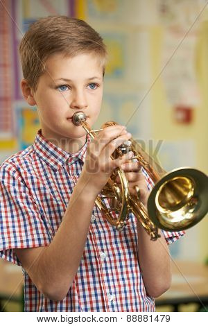 Boy Learning To Play Trumpet In School Music Lesson