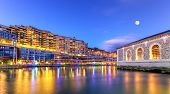 BFM buildings and Rhone river by night with full moon, Geneva, Switzerland, HDR poster