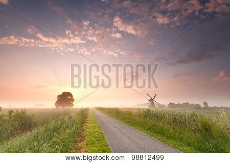 Beautiful Sunrise On Dutch Farmland With Windmill