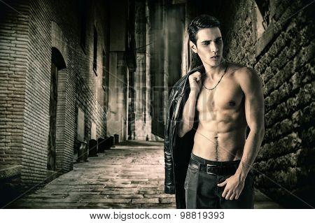 Portrait of a Young Vampire Man in an Open Black Leather Jacket, Showing his Chest and Abs, Looking to Right, on Dark Background. poster