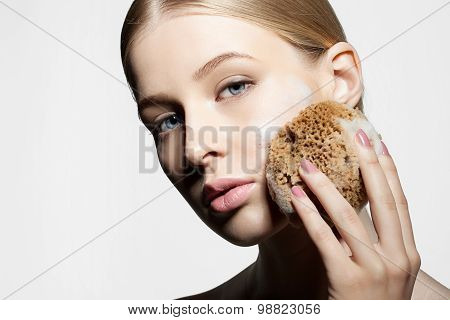 Woman cleans and exfoliates the skin with a natural sponge foam face on a white background close-up poster